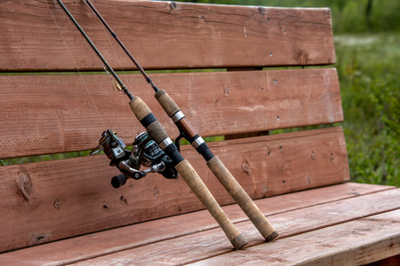Two fishing poles close up on a bench