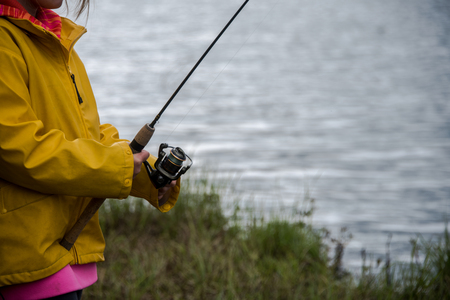 Young girl in a yellow raincoat fishing beside a lake
