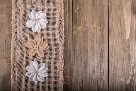 Three burlap flowers on burlap stripe on wood background with space