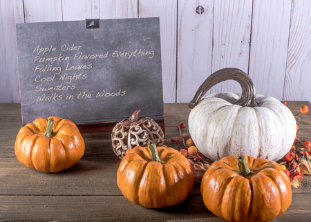 Chalkboard with list of autumn items and five pumpkins