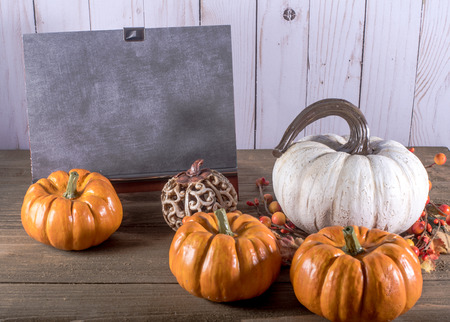 Blank Chalkboard with five pumpkins against white wooden background Zdjęcie Seryjne