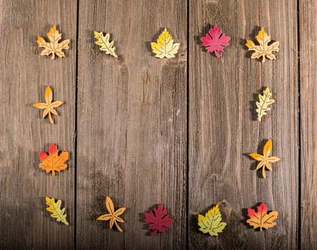 Wooden autumn leaves border on wooden background with space