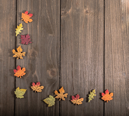 Wooden autumn leaves in a corner pattern on wood with blank space