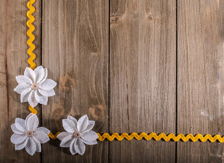 Burlap flowers and yellow rickrack for a corner border on wood