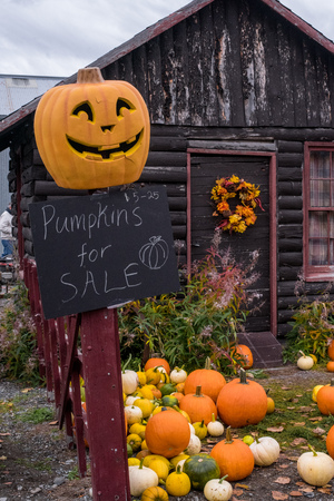 Pumpkins for sale in front of rustic cabin