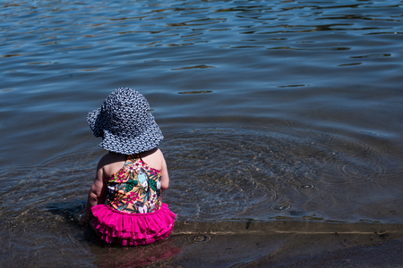 Baby girl in bright colored swim suit sitting in the water at the edge of a lake Zdjęcie Seryjne
