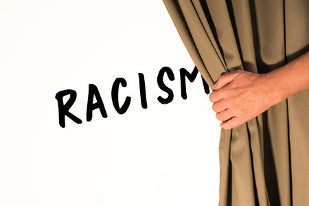 The word Racism being revealed from behind a curtain