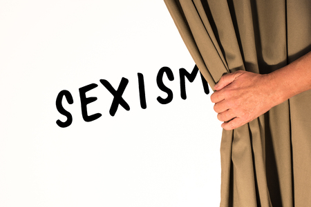 The word Sexism being revealed from behind a curtain Zdjęcie Seryjne