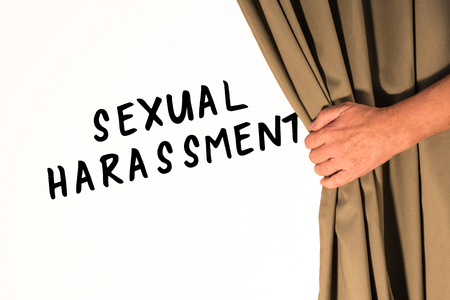 The words Sexual Harasment being revealed from behind a curtain