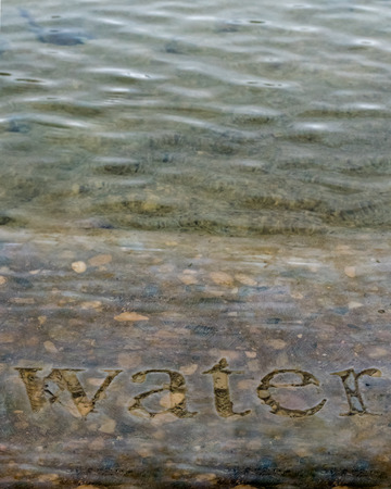 The Word Water carved into stone in a fountain