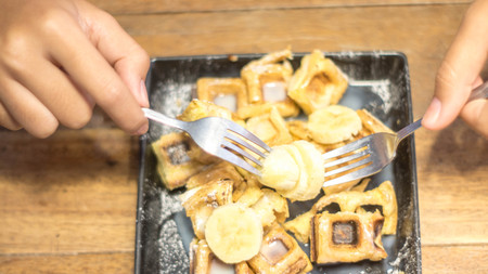 field depth: Toast topped with sliced bananas, nuts, egg, cream cheese sauce. Extreme shallow depth of field with selective focus on toast and some blur on corner of plate. Woman  man using a fork to eat. Stock Photo