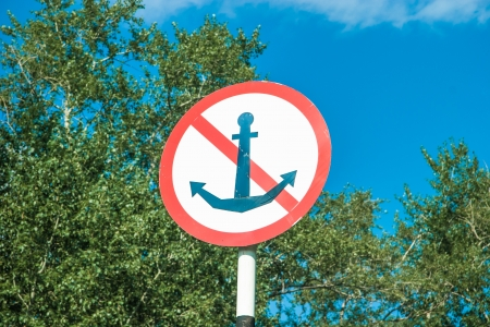 Marine NO anchor sign in front of trees photo