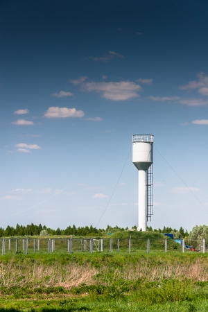 Water tower painted in white against blue sky photo
