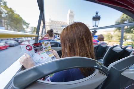turistic: Young woman with map in turistic bus in Barcelona