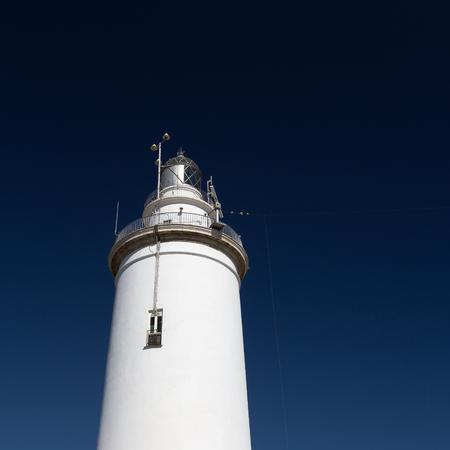 guiding light: White lighthouse in Malaga, Spain against the blue sky