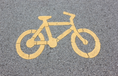 The white bicycle sign on gray asphalt  photo