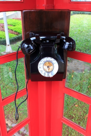Model old telephone in telephone booth. photo