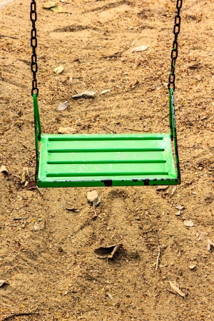 The swing in park for kids play it have green. photo