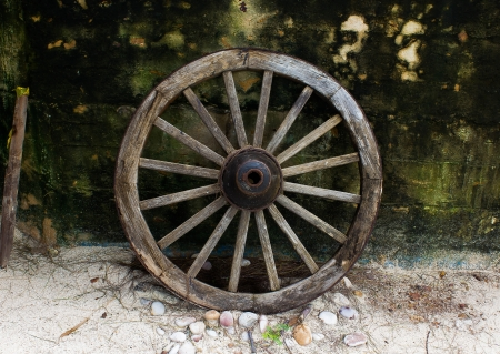 A decorative wagon wheel to the beautiful beach. Stock Photo - 18514345