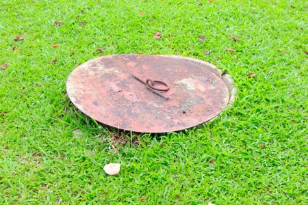 manhole cover  on garden it old and rost. Stock Photo