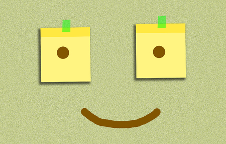 2 sticky note have eyes inside and smile on board Stock Photo