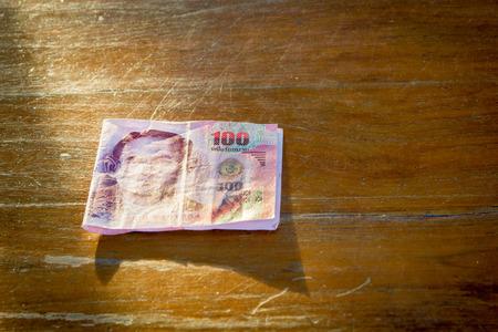 bill 100 bath of thailand on wood flor in sunlight