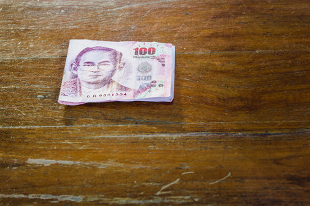 Bill 100 bath of thailand on wood floor Stock Photo