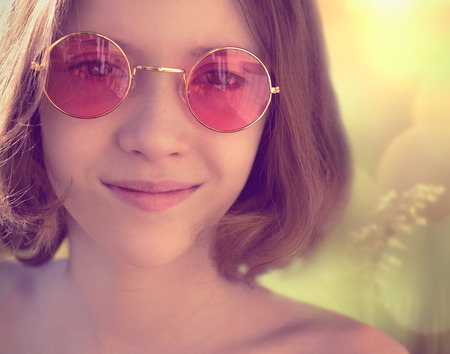 round face: A smiling girl in pink glasses Stock Photo
