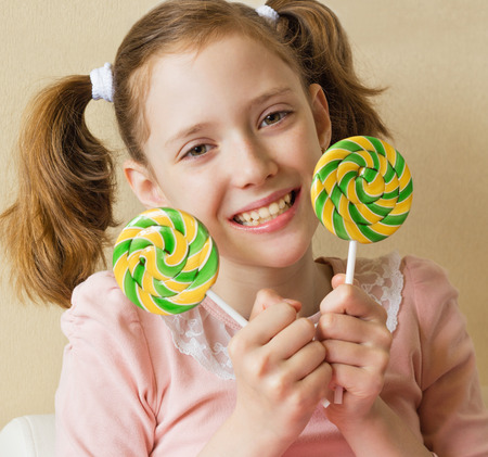 pigtails: The girl smiles and holds two Lollipop in his hands
