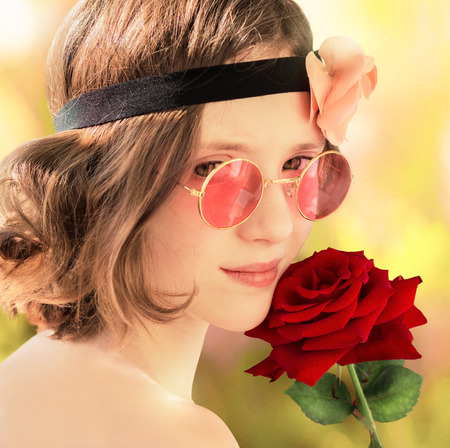 10 12 years: Girl in pink glasses with a red rose in his hand  Stock Photo