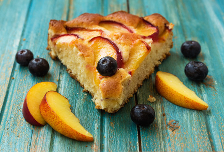 A slice of peach pie with blueberry on the background of wood photo