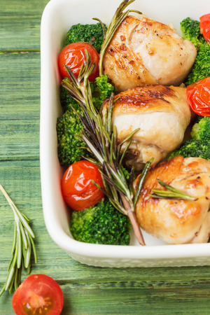 Chicken legs with cherry tomatoes, broccoli, rosemary in a white bowl on the background of the tree  photo