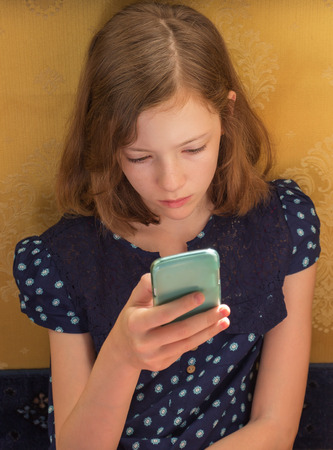 11: The child is reading a text message on a mobile phone