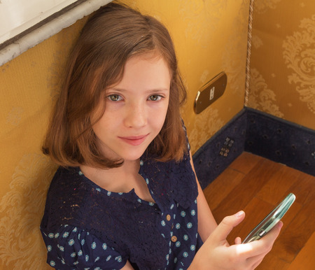 11: Thoughtful girl holding a cell phone sitting on the floor near the wall outlet