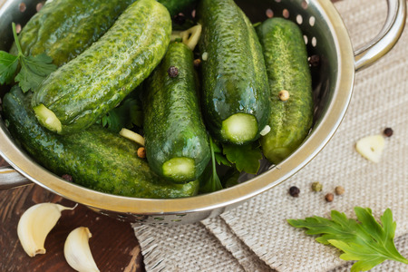 a colander: Salted cucumbers  Cucumbers with low content of salt in the colander, on wooden background