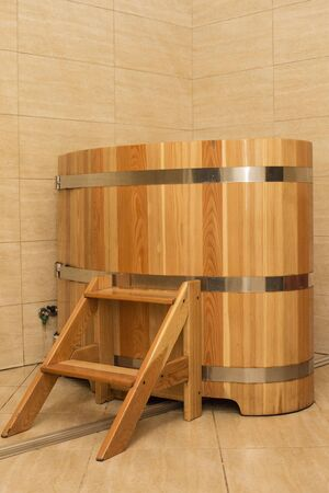 Spa hot wooden tub with stairs. Modern bathhouse. Rest and relaxation.