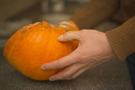 A man holds a mouldy pumpkin. Autumn vegetable in hand.