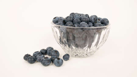 Ripe blueberries in crystal dish. Isolated on white background. Closeup blue berry