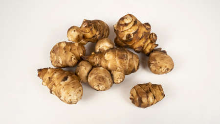 Jerusalem Artichokes in a white background. Fresh root vegetable, topinambour, food for vegetarian.