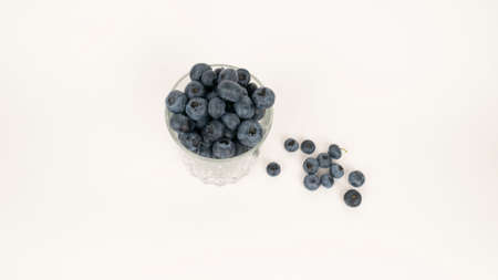 Ripe blueberries in crystal glass top view. Isolated on white background. Closeup blue berry 版權商用圖片