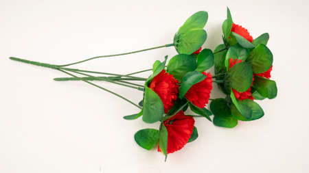 Artificial textile red carnations on white background. Dead monument decoration