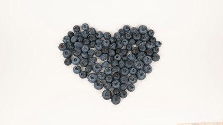 Raw blueberry heart shape on white background. Vegetarian food, blue berry crop 版權商用圖片