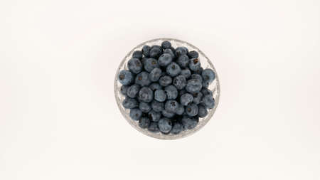 Ripe blueberries in glass bowl top view. Isolated on white background. Closeup blue berry