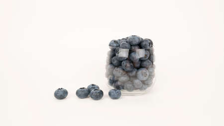 Ripe blueberries in glass close up. Isolated on white background health eating