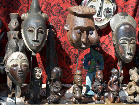A selection of African masks and statues at a flea market on a red background