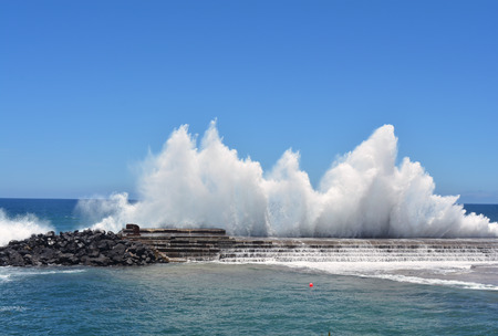Vibrant image of a wave breaking on a harbour wall Stock Photo