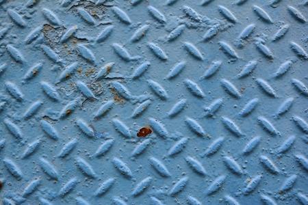 diamond plate background: A weathered blue diamond plate background with flecks of rust