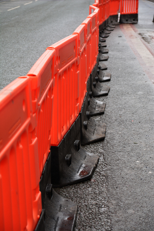 A photo of a temporary walkway with plastic safety barriers on a roadwork site.