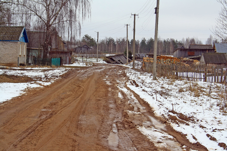 barns winter: rural ground dirty road and fallen barn Stock Photo