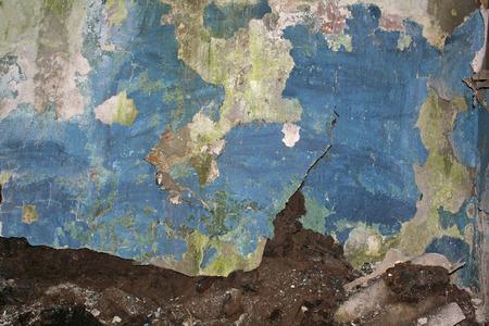 dilapidated: peeling blue plaster on dilapidated wall